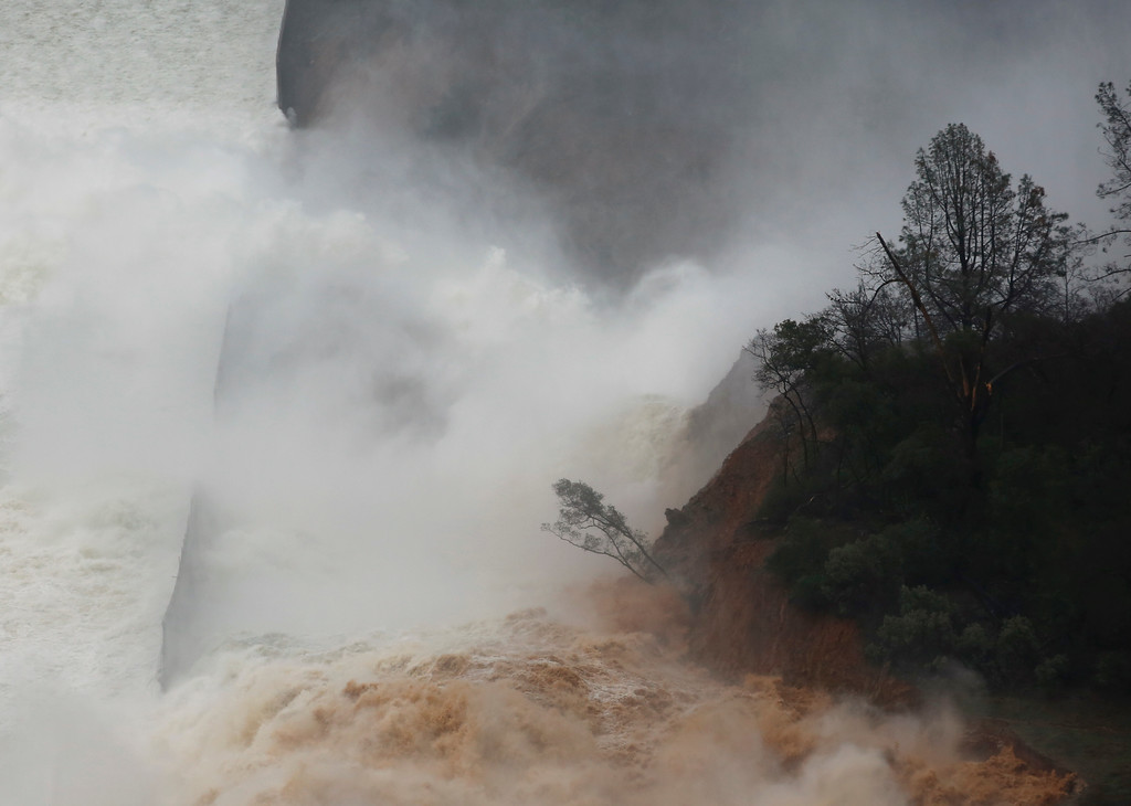 """. Water flows through break in the wall of the Oroville Dam spillway, Thursday, Feb. 9, 2017, in Oroville, Calif. The torrent chewed up trees and soil alongside the concrete spillway before rejoining the main channel below. Engineers don\'t know what caused what state Department of Water Resources spokesman Eric See called a \""""massive\"""" cave-in that is expected to keep growing until it reaches bedrock. (AP Photo/Rich Pedroncelli)"""