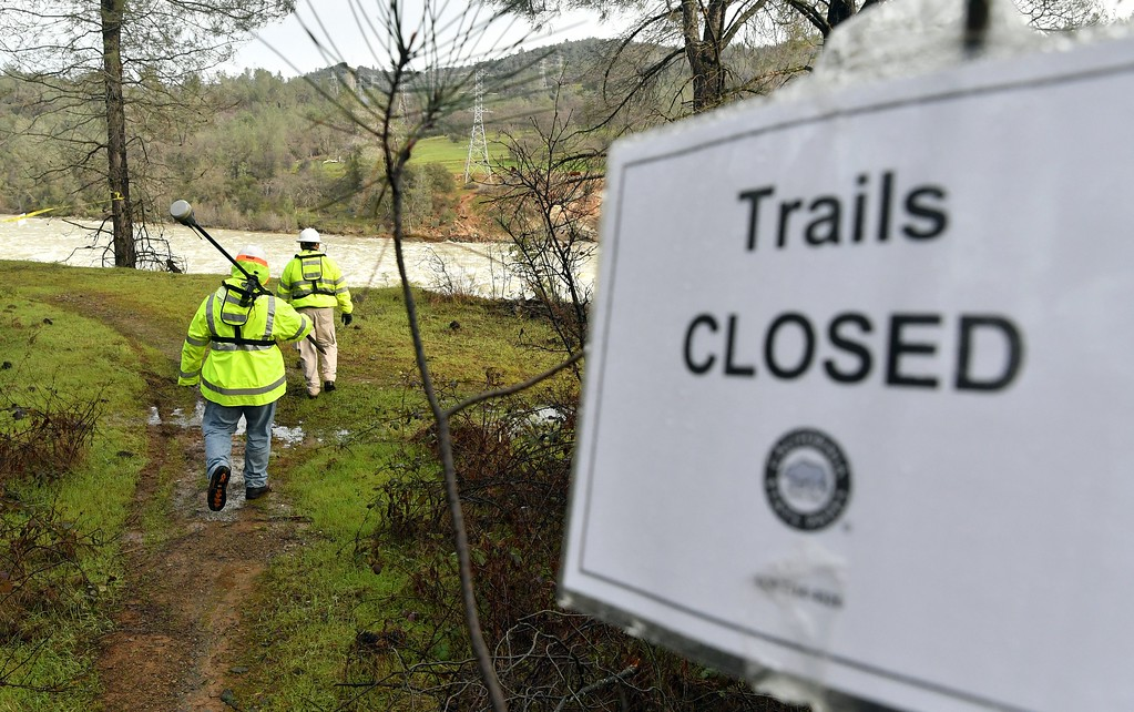 . Water utility workers work their way down to an eroded hillside to measure depth as rushing water discharges down a spillway as an emergency measure at the Oroville Dam in Oroville, California on February 13, 2017. Almost 200,000 people were under evacuation orders in northern California Monday after a threat of catastrophic failure at the United States\' tallest dam. Officials said the threat had subsided for the moment as water levels at the Oroville Dam, 75 miles (120 kilometers) north of San Francisco, have eased. But people were still being told to stay out of the area.  / AFP / Josh Edelson        (Photo credit should read JOSH EDELSON/AFP/Getty Images)