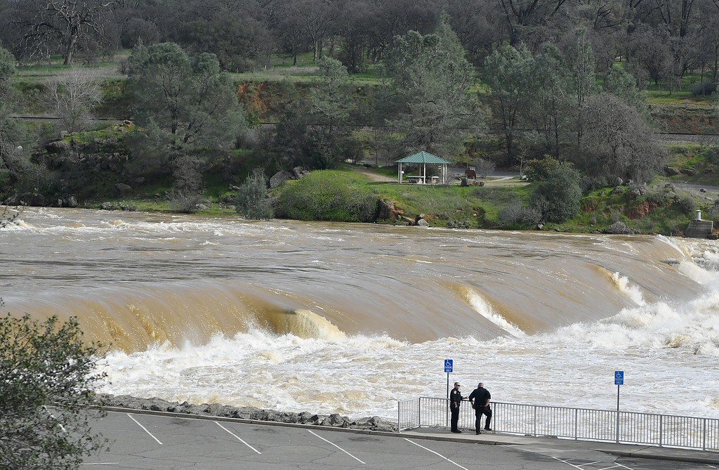 . Police officers confer as the Oroville Dam releases water down a spillway as an emergency measure in Oroville, California on February 13, 2017. Almost 200,000 people were under evacuation orders in northern California Monday after a threat of catastrophic failure at the United States\' tallest dam. Officials said the threat had subsided for the moment as water levels at the Oroville Dam, 75 miles (120 kilometers) north of San Francisco, have eased. But people were still being told to stay out of the area. (JOSH EDELSON/AFP/Getty Images)