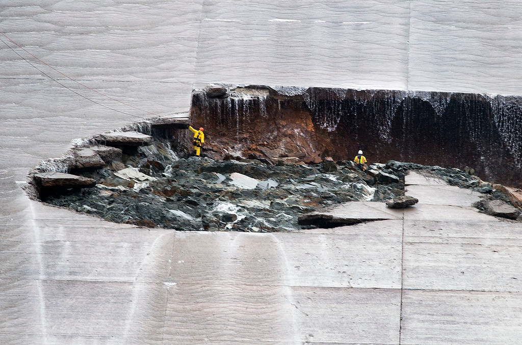 . Water trickles down as workers inspect part of the Lake Oroville spillway failure on Wednesday, Feb. 8, 2017 in Oroville, Calif. The Department of Water Resources said the erosion at Lake Oroville does not pose a threat to the earthen dam or public safety, and the reservoir has plenty of capacity to handle the continuing rain. (Randy Pench/The Sacramento Bee via AP)