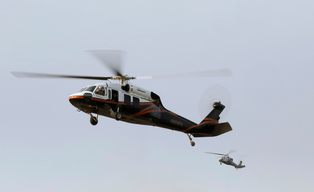 . A pair of helicopters come in for a landing at a staging area near the Oroville Dam, Monday, Feb. 13, 2017, in Oroville, Calif. State officials have discussed using helicopters to drop loads of rock on the damaged emergency spillway of the dam. (AP Photo/Rich Pedroncelli)