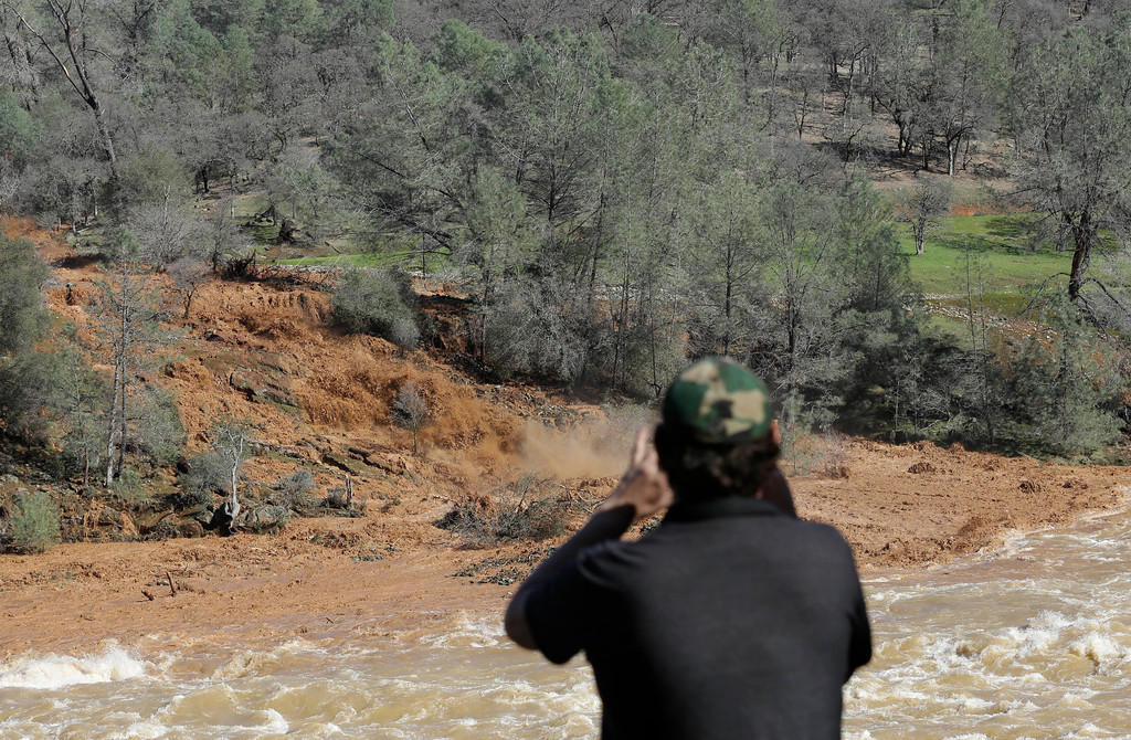 . E. Knight uses his smartphone to record muddy water rushing down the emergency spillway at Oroville Dam, Saturday, Feb. 11, 2017, in Oroville, Calif. Water started flowing over the emergency spillway at the nation\'s tallest dam for the first time Saturday after erosion damaged the Northern California dam\'s main spillway. (AP Photo/Rich Pedroncelli)