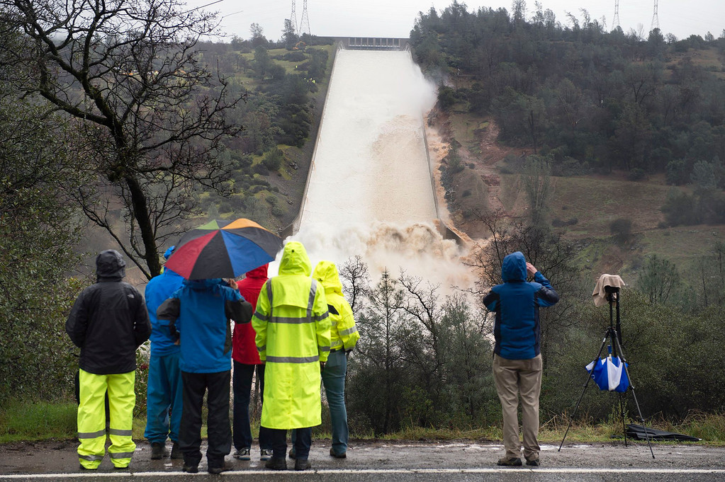. Department of Water Resources workers and members of the media watch as up to 20,000 cubic feet per second of water is released over the damaged spillway on Wednesday, Feb. 8, 2017 in Oroville, Calif. The Department of Water Resources said the erosion at Lake Oroville does not pose a threat to the earthen dam or public safety, and the reservoir has plenty of capacity to handle the continuing rain. (Randy Pench/The Sacramento Bee via AP)