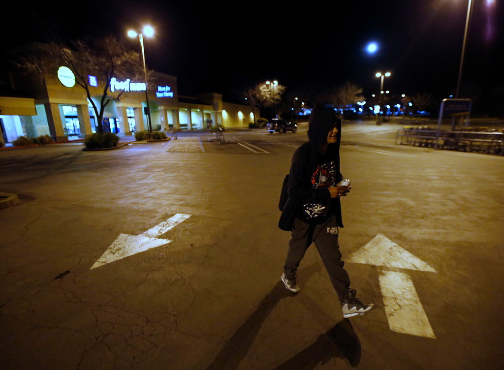 . Angie Varrera walks across an empty parking lot after finding the grocery store she stopped at closed due to an evacuation order Sunday, Feb. 12, 2017, in Oroville, Calif. Thousands of Northern California residents remain under evacuation orders after authorities warned an emergency spillway in the country\'s tallest Oroville Dam was in danger of failing Sunday and unleashing uncontrolled flood waters on towns below. (AP Photo/Rich Pedroncelli)