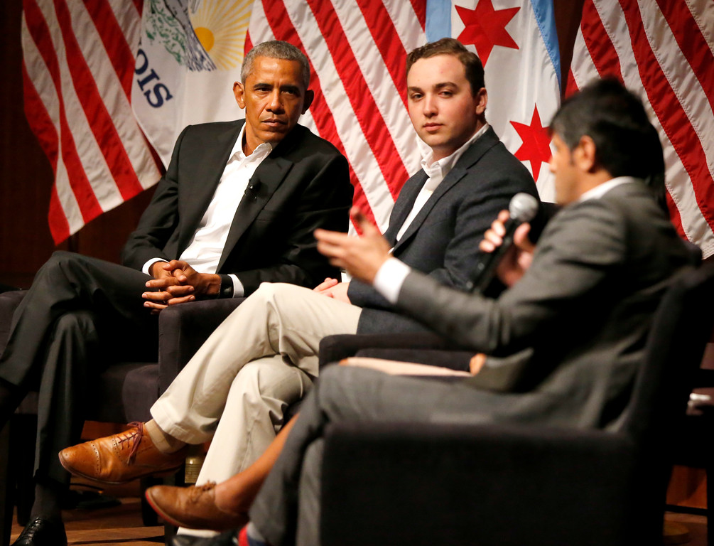 . Former President Barack Obama and Max Freedman, center, listen to Harish Patel speaks during a conversation on civic engagement and community organizing, Monday, April 24, 2017, at the University of Chicago in Chicago. It\'s the former president\'s first public event of his post-presidential life in the place where he started his political career. (AP Photo/Charles Rex Arbogast)