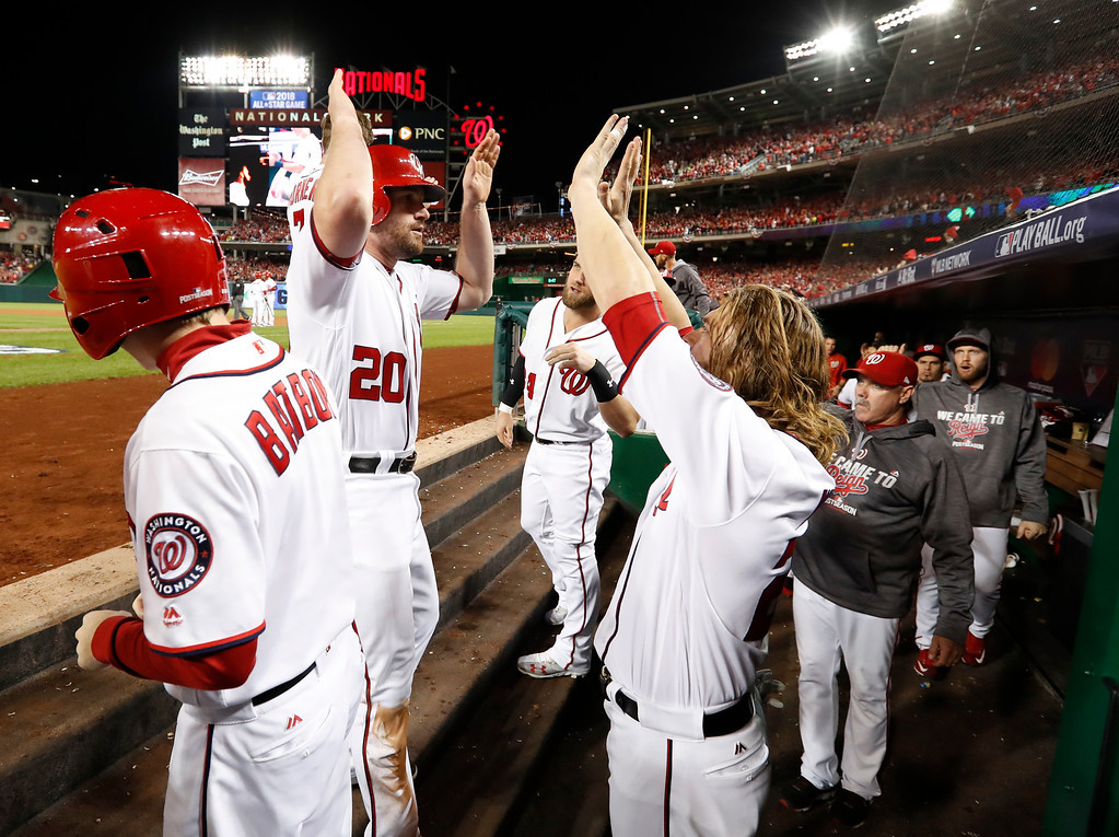 . Washington Nationals\' Daniel Murphy (20) celebrates in the dugout with teammates Jayson Werth (28) and Bryce Harper (34) after scoring during the second inning in Game 5 of baseball\'s National League Division Series against Los Angeles Dodgers, at Nationals Park, Thursday, Oct. 13, 2016, in Washington. (AP Photo/Alex Brandon)