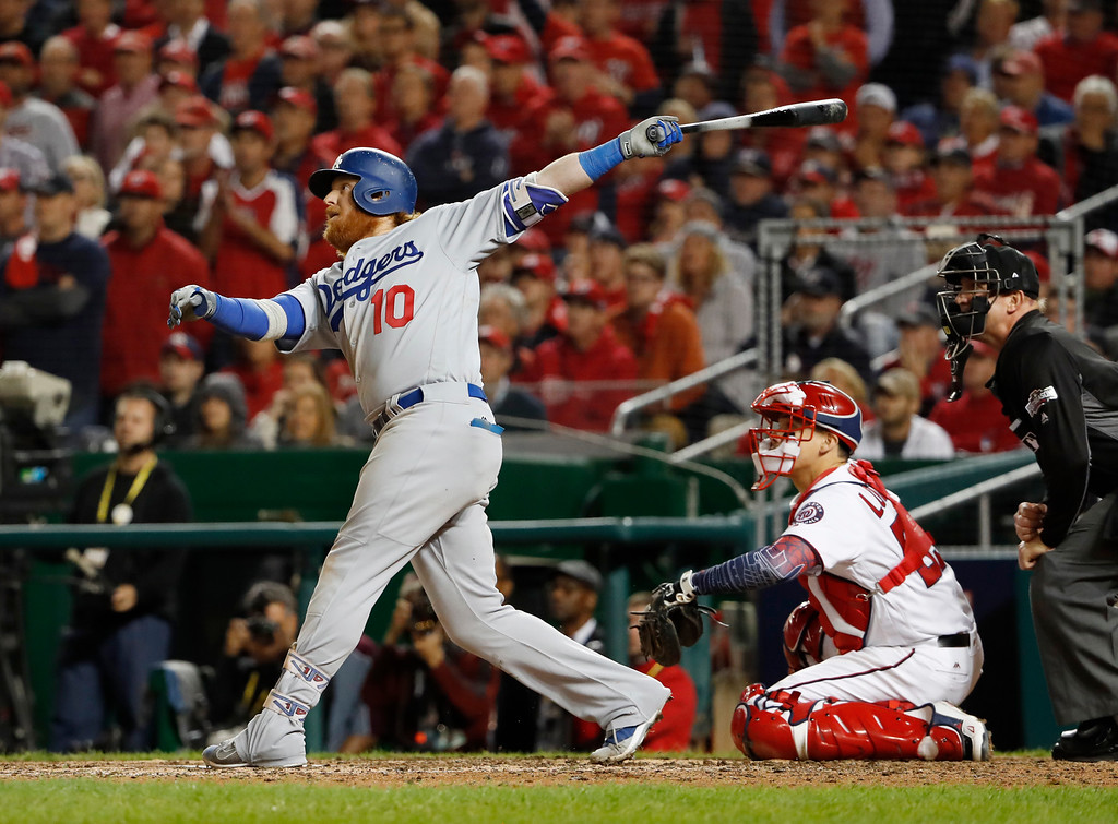 . Los Angeles Dodgers\' Justin Turner watches his two-run triple during the seventh inning as Washington Nationals catcher Jose Lobaton (59) watches during Game 5 of baseball\'s National League Division Series at Nationals Park, Thursday, Oct. 13, 2016, in Washington. (AP Photo/Pablo Martinez Monsivais)