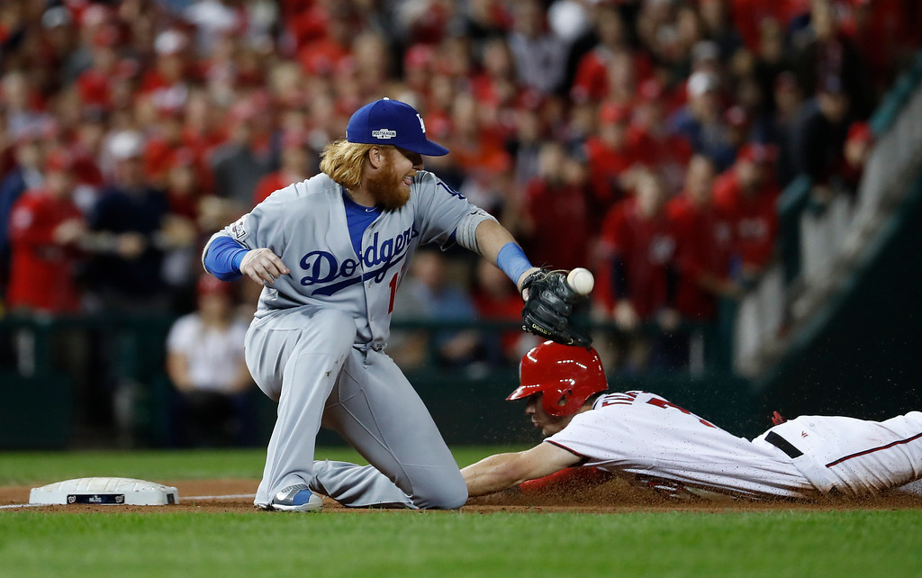 . Washington Nationals\' Trea Turner (7) slides safely into third as Los Angeles Dodgers third baseman Justin Turner (10) takes the throw during the third inning in Game 5 of baseball\'s National League Division Series, at Nationals Park, Thursday, Oct. 13, 2016, in Washington. (AP Photo/Alex Brandon)