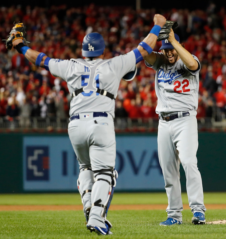 . Los Angeles Dodgers pitcher Clayton Kershaw (22) and catcher Carlos Ruiz celebrate after Washington Nationals\' Wilmer Difo struck out to end Game 5 of a baseball National League Division Series, at Nationals Park early Friday, Oct. 14, 2016, in Washington. The Dodgers won 4-3. (AP Photo/Alex Brandon)