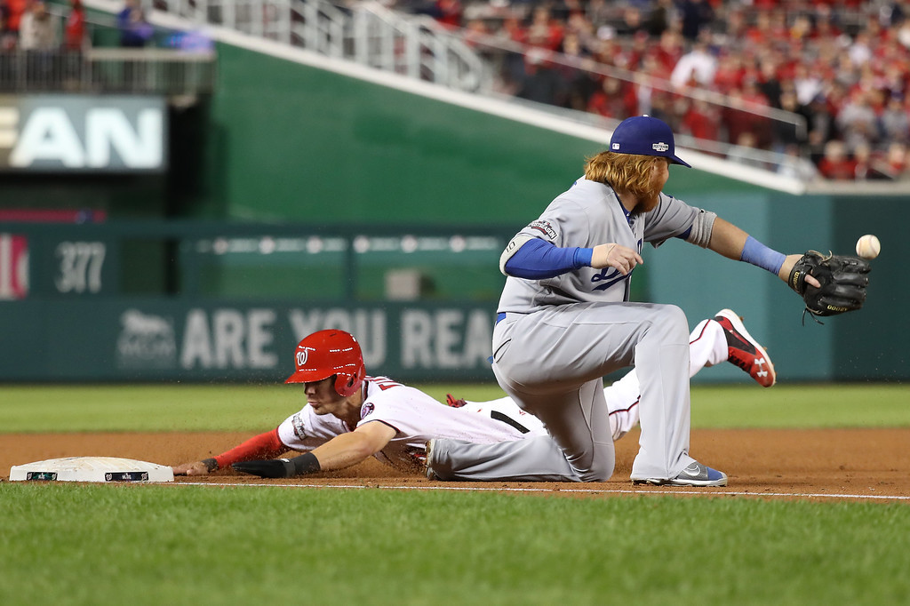 . WASHINGTON, DC - OCTOBER 13: Trea Turner #7 of the Washington Nationals dives into third base against Justin Turner #10 of the Los Angeles Dodgers in the third inning during game five of the National League Division Series at Nationals Park on October 13, 2016 in Washington, DC. (Photo by Rob Carr/Getty Images)