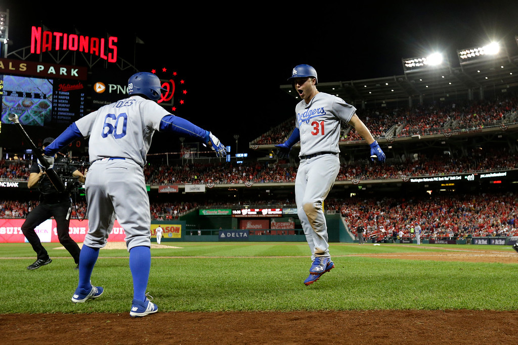 . WASHINGTON, DC - OCTOBER 13: Joc Pederson #31 of the Los Angeles Dodgers celebrates with teammate Andrew Toles #60 after hitting a solo home run in the seventh inning against the Washington Nationals during game five of the National League Division Series at Nationals Park on October 13, 2016 in Washington, DC. (Photo by Rob Carr/Getty Images)
