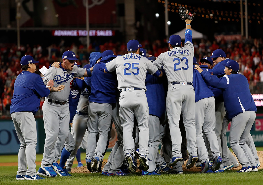 . The Los Angeles Dodgers celebrate a 4-3 win over the Washington Nationals in Game 5 of a baseball National League Division Series, at Nationals Park early Friday, Oct. 14, 2016, in Washington. (AP Photo/Alex Brandon)
