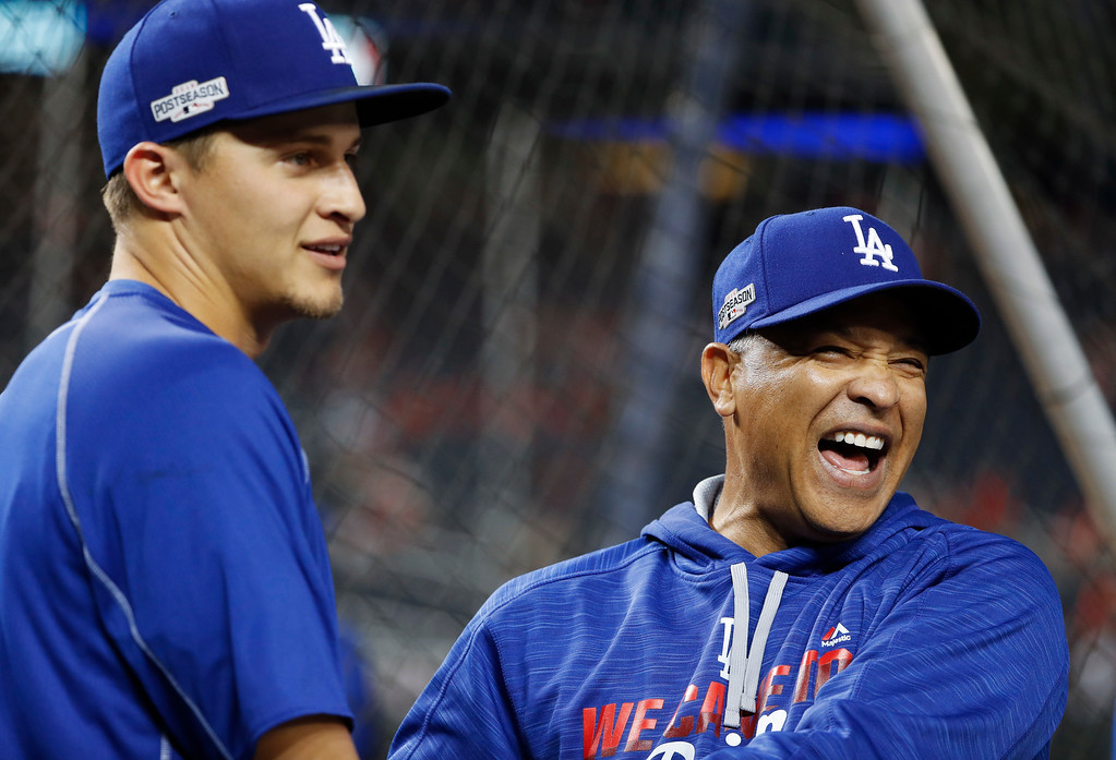 . Los Angeles Dodgers manager Dave Roberts, right, jokes with shortstop Corey Seager during batting practice before Game 5 of baseball\'s National League Division Series against the Washington Nationals at Nationals Park, Thursday, Oct. 13, 2016, in Washington. (AP Photo/Pablo Martinez Monsivais)