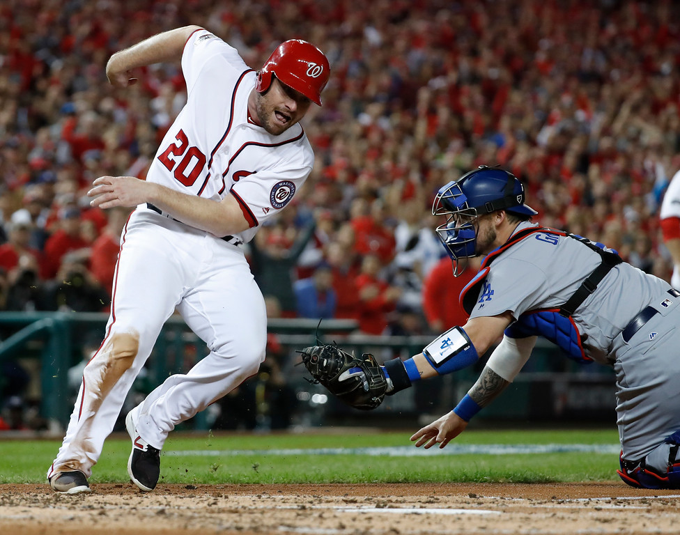 . Washington Nationals\' Daniel Murphy (20) runs around the tag from Los Angeles Dodgers catcher Yasmani Grandal (9) to score during the second inning in Game 5 of baseball\'s National League Division Series, at Nationals Park, Thursday, Oct. 13, 2016, in Washington. (AP Photo/Alex Brandon)