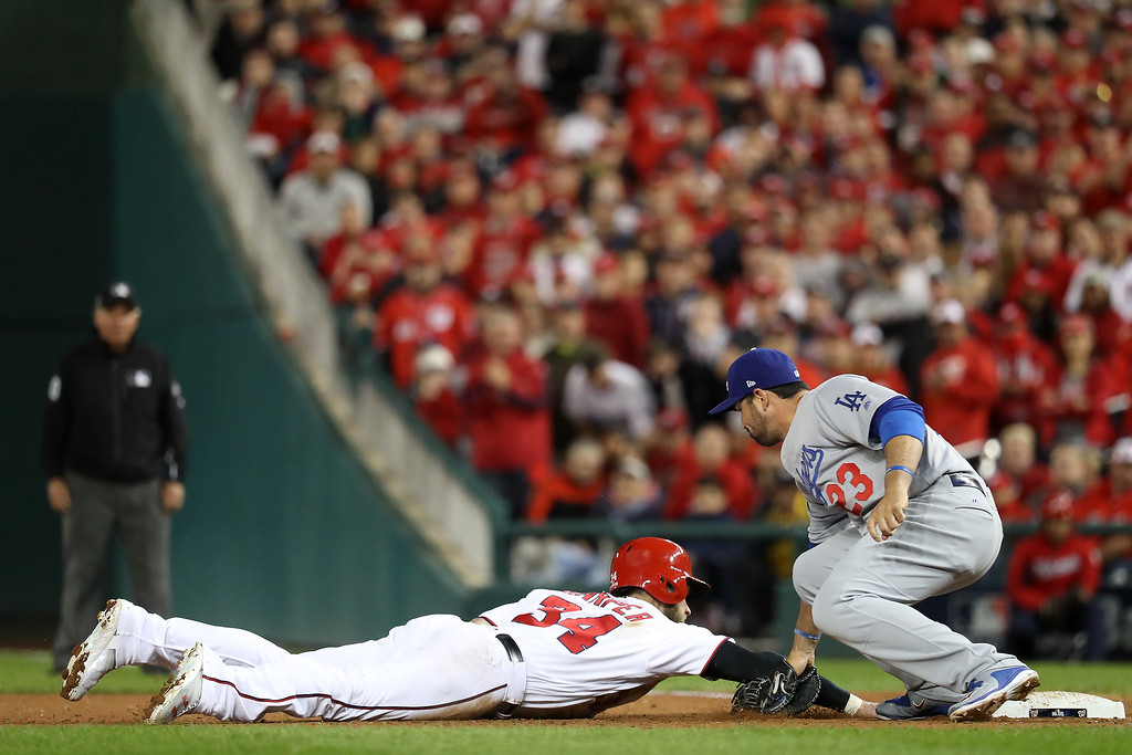 . WASHINGTON, DC - OCTOBER 13: Bryce Harper #34 of the Washington Nationals is picked off at first base by Adrian Gonzalez #23 of the Los Angeles Dodgers for the third out of the fifth inning during game five of the National League Division Series at Nationals Park on October 13, 2016 in Washington, DC. (Photo by Rob Carr/Getty Images)