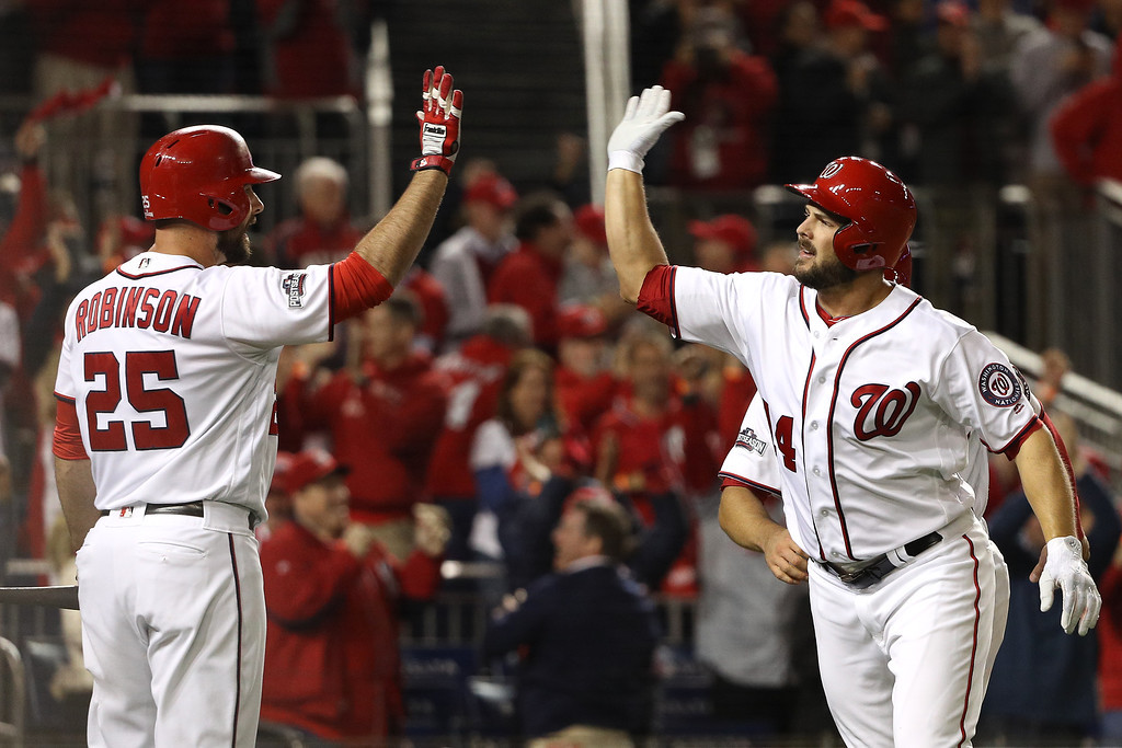. WASHINGTON, DC - OCTOBER 13: Chris Heisey #14 of the Washington Nationals celebrates with teammate Clint Robinson #25 after hitting a two run home run in the seventh inning against the Los Angeles Dodgers during game five of the National League Division Series at Nationals Park on October 13, 2016 in Washington, DC. (Photo by Patrick Smith/Getty Images)