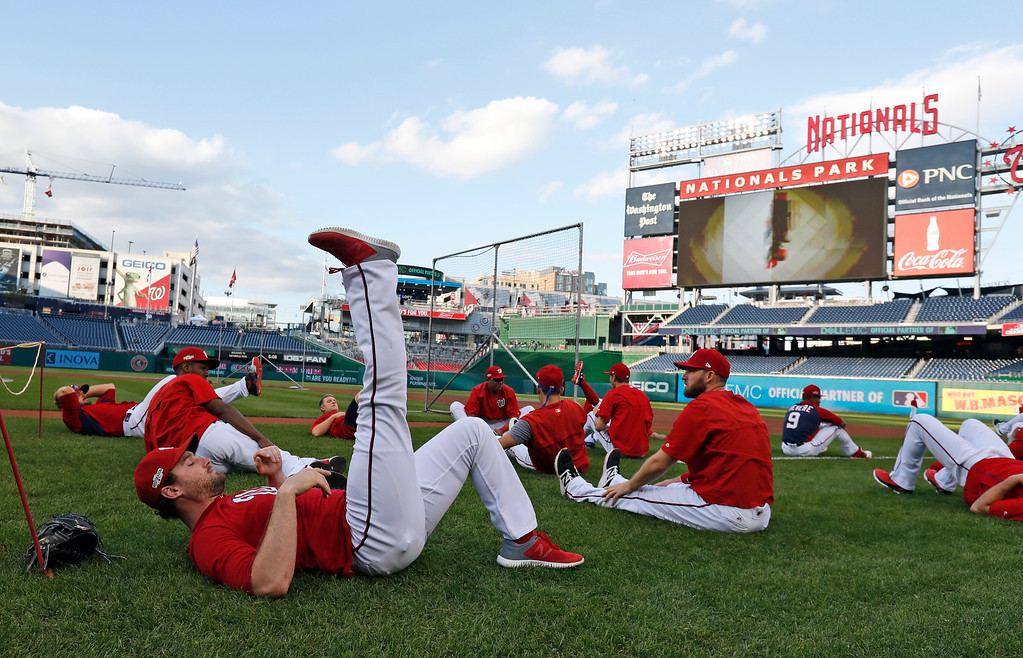 . Washington Nationals second baseman Daniel Murphy, front left, and others warm up during batting practice before Game 5 of baseball\'s National League Division Series against the Los Angeles Dodgers at Nationals Park, Thursday, Oct. 13, 2016, in Washington. (AP Photo/Alex Brandon)