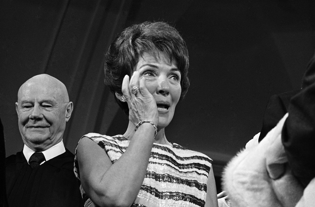 . Nancy Reagan, California\'s new first lady, brushes away a tear early, Jan. 2, 1967 in Sacramento, Calif., after her husband was sworn in as the state\'s 33rd governor. Gov. Ronald Reagan took the oath of office in Sacramento\'s capitol rotunda in post-midnight ceremony. (AP Photo)