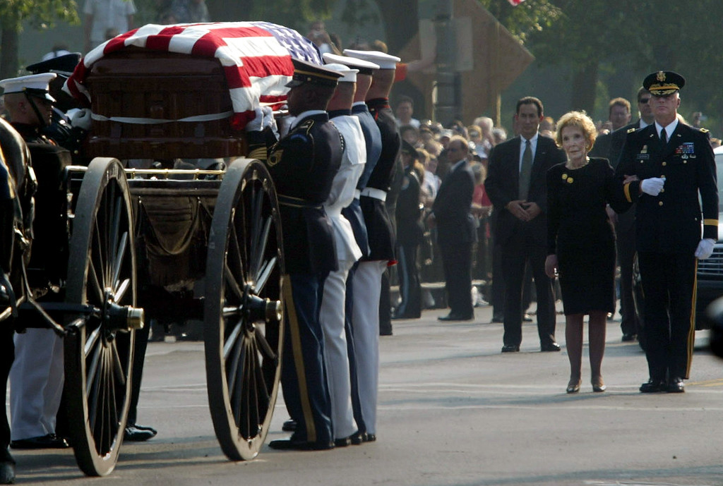 . Nancy Reagan, second from right, watches the arrival of her late husband, former President Ronald Reagan, as it makes its way to the U.S. Capitol, Wednesday, June 9, 2004, in Washington.(AP Photo/Lawrence Jackson)