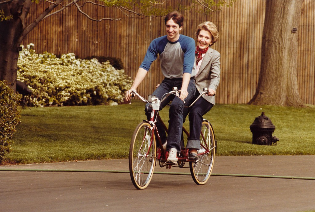 . First Lady Nancy Reagan riding a tandem bicycle with son Ron Reagan on the south grounds of the White House, Washington, DC, 4/22/81  Photo Credit: The Ronald Reagan Presidential Library and Museum