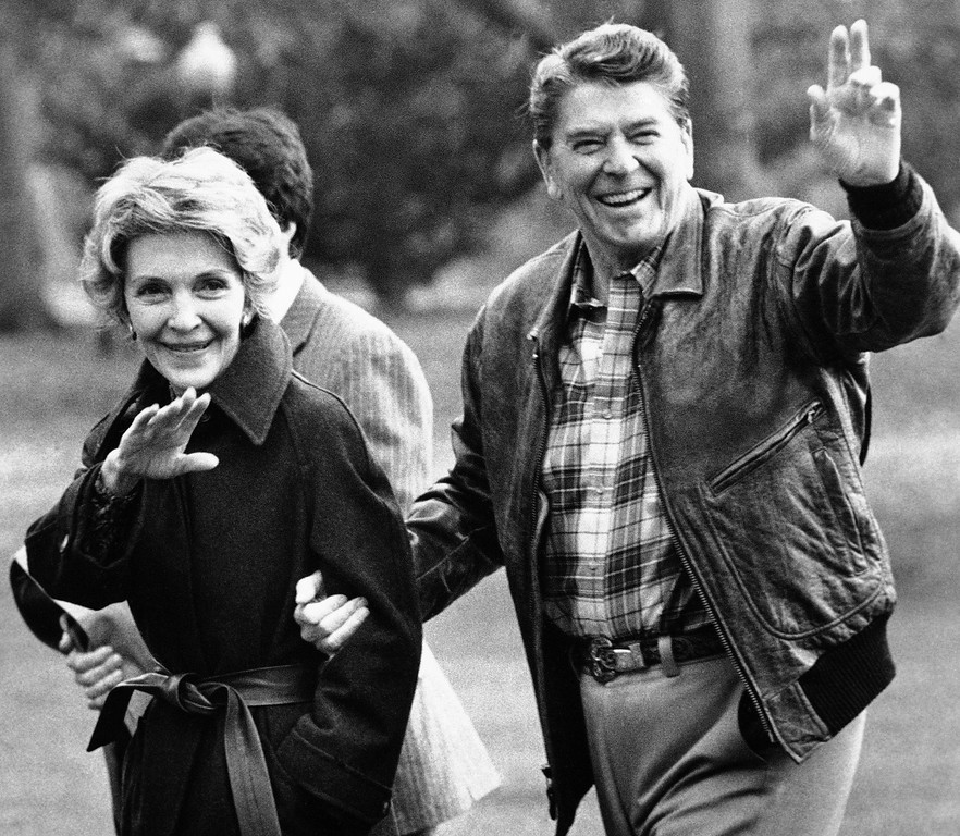. Pres. Ronald Reagan, right, and Mrs. Nancy Reagan wave to photographers as they return to the White House after spending the weekend at Camp David, Md., Sunday, Dec. 2, 1984, Washington, D.C. The Reagans are scheduled to host a reception for the Kennedy Center honorees at the White House this evening. (AP Photo)