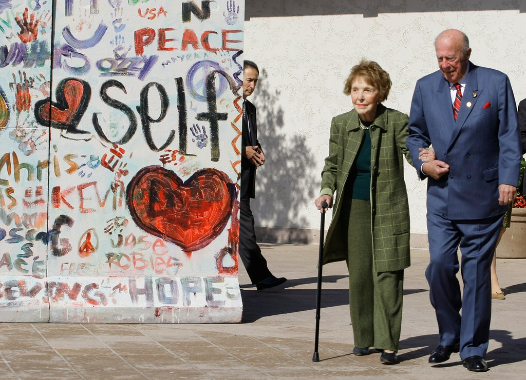 . Former First Lady Nancy Reagan, left, is helped by George Shultz, Secretary of State under President Reagan, as they arrive at The Ronald Reagan Presidential Library in Simi Valley, Calif. on Friday, November 6, 2009. The Ronald Reagan Presidential Foundation and Library and The Heritage Foundation commemorate the 20th anniversary of the fall of the Berlin Wall and the advent of freedom and democracy in Eastern Europe. (AP Photo/Damian Dovarganes)