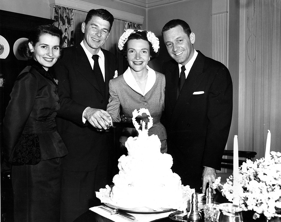 . Actor Ronald Reagan and his bride, actress Nancy Davis, cut their wedding cake after their marriage at the non-sectarian Little Brown Church of the Valley in North Hollywood, Ca., March 4, 1952.  With them are actress Brenda Marshall, left, and her husband, actor William Holden.  (AP Photo)
