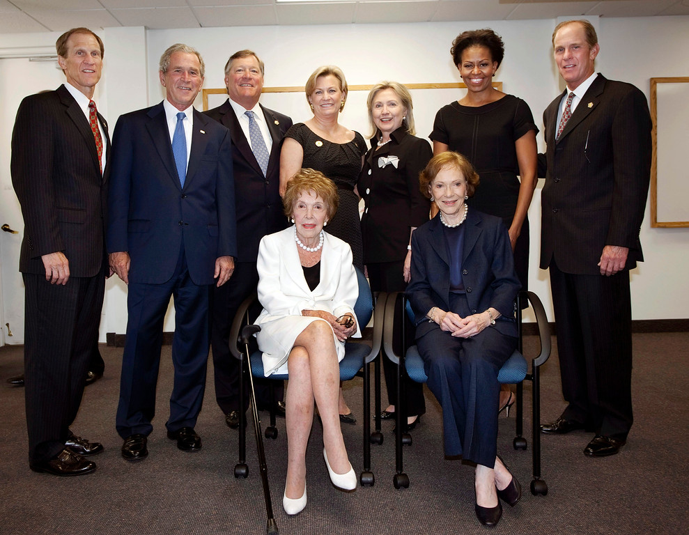 . In this image released by the Gerald R. Ford Library and Museum, (L-R) Mike Ford, former President George W. Bush, Jack Ford, Susan Ford Bales, former first lady and Secretary of State Hillary Rodham Clinton, first lady Michelle Obama, and Steve Ford stand as former first lady Nancy Reagan and former first lady Rosalynn Carter sit as they gather for a photo before the funeral of former first lady Betty Ford at St. Margaret\'s Episcopal Church July 12, 2011 in Palm Desert, California. (Photo by David Hume Kennerly/Gerald R. Ford Library and Museum via Getty Images)