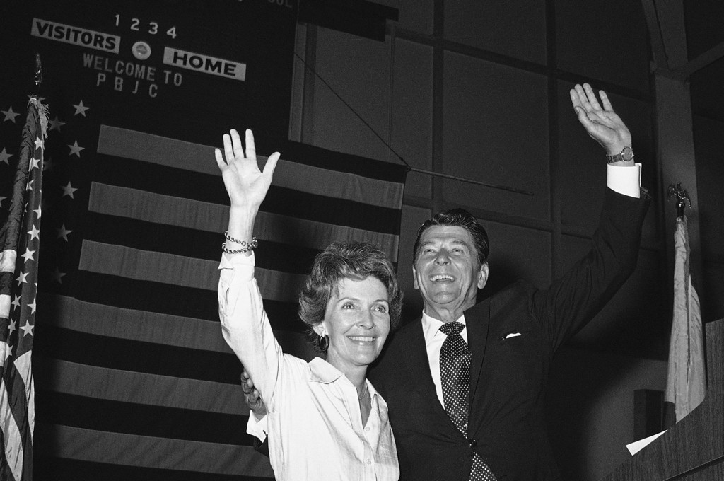 . Former California Governor, Ronald Reagan, Republican candidate for President and his wife Nancy, raises their arms in response to a loud applause as they stand on the podium on March 8, 1976 in Lake Worth. The rally for Reagan, was held last night at the Palm Beach Junior College. (AP Photo)