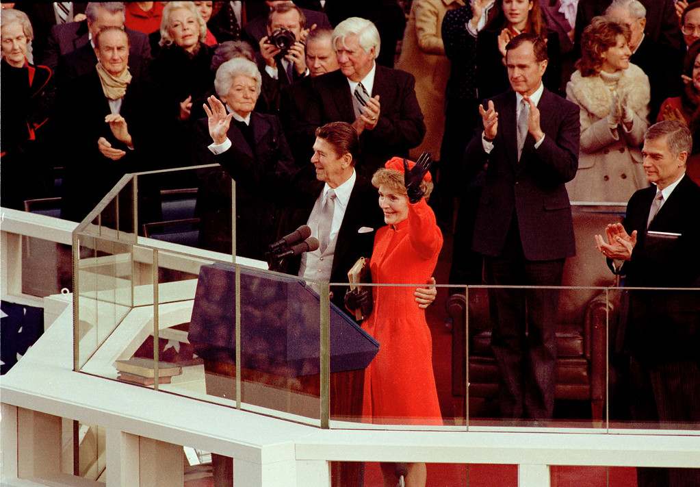 . U.S. President Ronald Reagan and his wife, first lady Nancy Reagan, wave to the crowd on the west front of the Capitol building in Washington, D.C., after he was sworn in as the nation\'s 40th president, Jan. 20, 1981.  Applauding behind the Reagans are House Speaker Thomas P. O\'Neill, left, Vice President George Bush, center, and Sen. Mark Hatfield, far right.  (AP Photo)