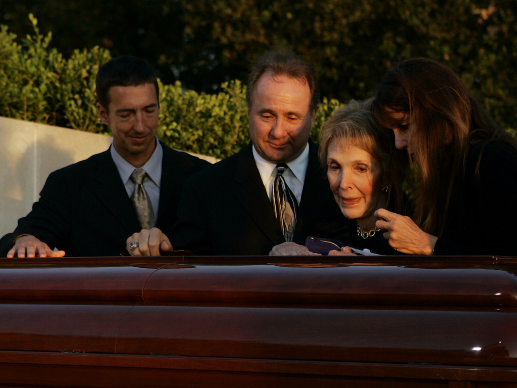 . Nancy Reagan is comforted by her children, Ron, left, Michael and Patti, right, beside the casket of her husband, President Ronald Reagan, after interment ceremonies at the Ronald Reagan Presidential Library in Simi Valley, Calif., Friday, June 11, 2004. (AP Photo/Kevork Djansezian, Pool)