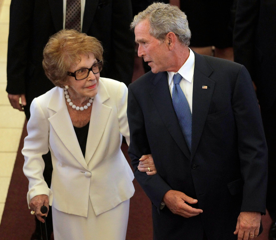 . Former first lady Nancy Reagan (L) is escorted by former President George W. Bush following the funeral for former first lady Betty Ford at St. Margaret\'s Episcopal Church July 12, 2011 in Palm Desert, California. (Photo by Jae C. Hong-Pool/Getty Images)