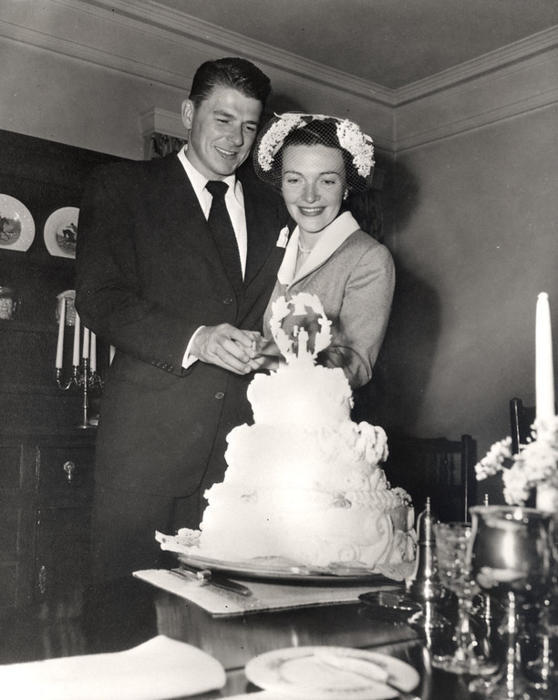 . Newlyweds Ronald and Nancy Reagan cutting their wedding cake at the home of Bill and Ardis Holden in Toluca Lake, California, 3/4/52.  Photo Credit: The Ronald Reagan Presidential Library Foundation