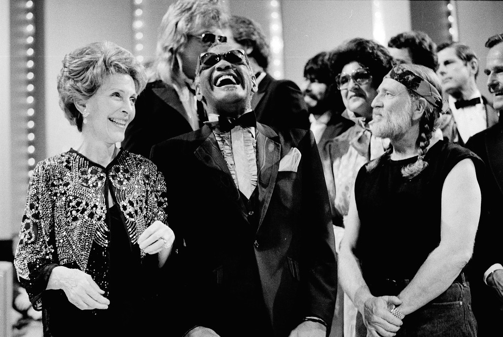 . Then-first lady Nancy Reagan, left, gets a laugh with Ray Charles, center, and Willie Nelson, right, and other entertainers at a salute to country music at Constitution Hall in Washington on March 16, 1983. (AP Photo/Ira Schwarz)
