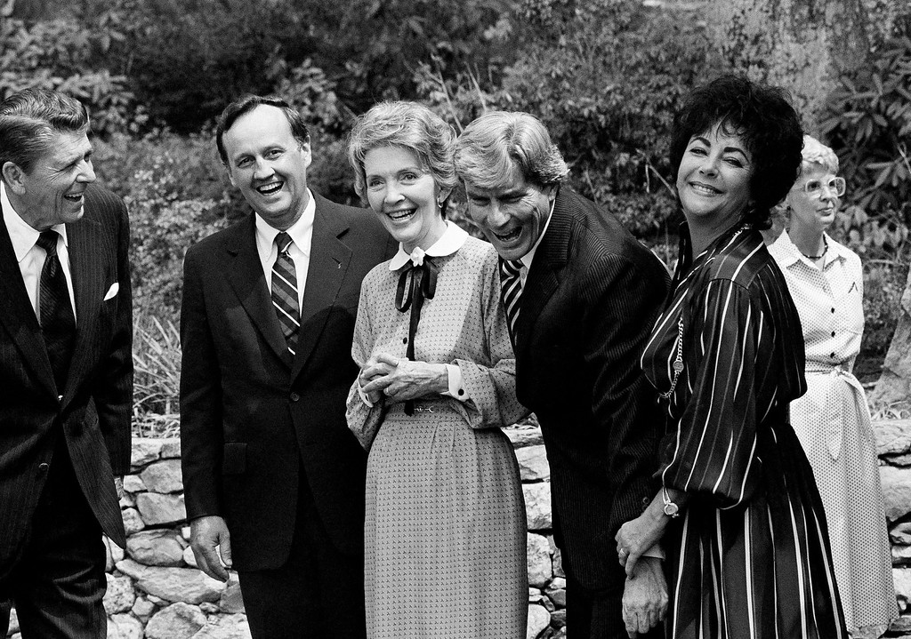 . Actress Elizabeth Taylor Warner looks pleased after she jokingly removed her husband, Sen. John Warner\'s hand from a picture in Middleburg, Va., Thursday, August 28, 1980, upon GOP presidential candidate Ronald Reagan\'s arrival for temporary residence. From left are: Reagan, Va. Gov. John N. Dalton, Mrs. Nancy Reagan, Warner, and Mrs. Warner. (AP Photo)