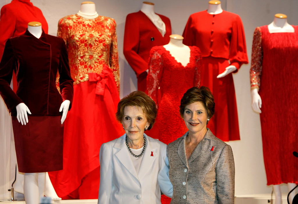 . Nancy Reagan, left, famous for her love of red dresses, and first lady Laura Bush, right, stand  together at the John F. Kennedy Center for the Performing Arts as they open an exhibit to promote a heart health campaign for women, in Washington, Thursday, May 12, 2005. They unveiled the The Heart Truth\'s First Ladies Red Dress Collection, a historic medley of red gowns, dresses and suits worn by first ladies since Lady Bird Johnson, to drawn awareness to a national campaign for women about heart disease. (AP Photo/J. Scott Applewhite)