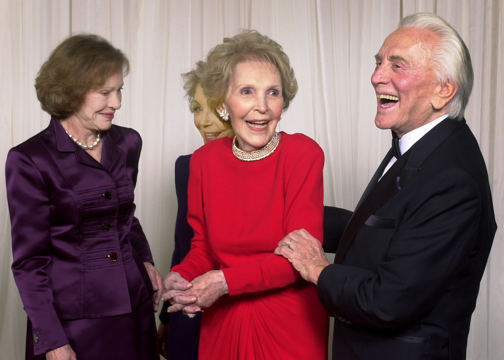 . Kirk Douglas, right, shares a happy moment with former first lady Nancy Reagan as his wife Anne Douglas, partly hidden, and former first lady Rosalynn Carter chat at a gala 20th anniversary fundraising event saluting Betty Ford and the Betty Ford Center Friday, Jan. 17, 2003, in Indian Wells, Calif.   (AP Photo/Reed Saxon)