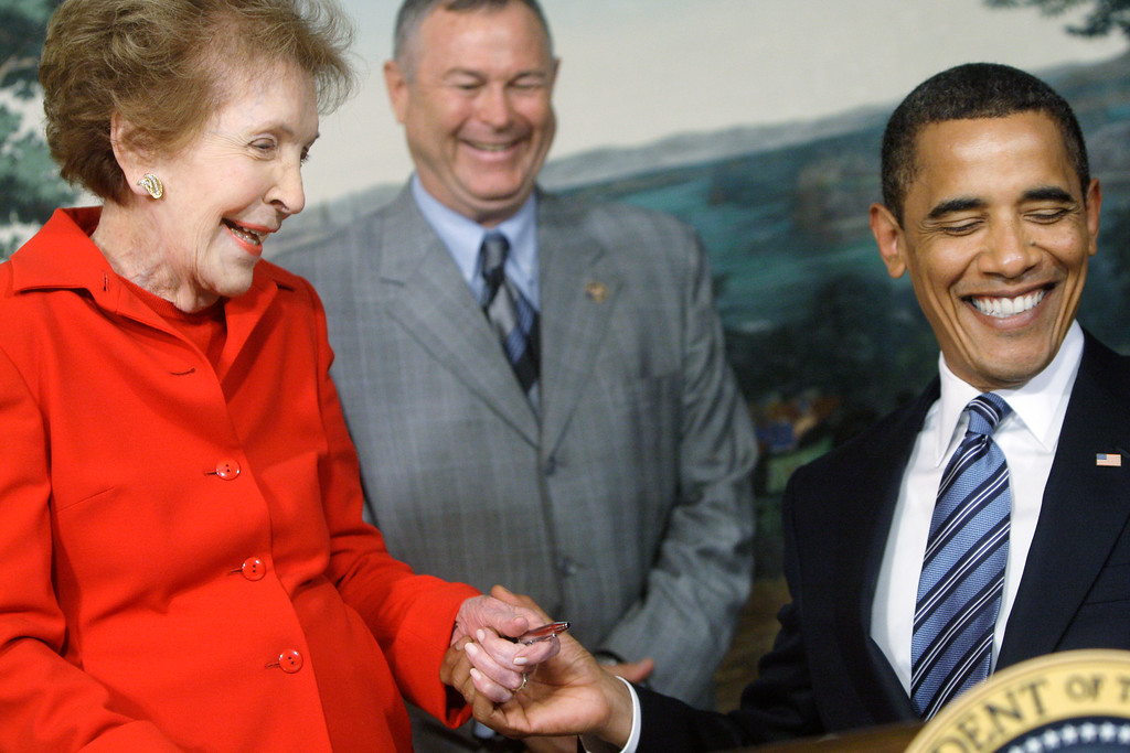 . Former first lady Nancy Reagan and President Barack Obama smile after Obama presented her with a pen after signing the Ronald Reagan Centennial Commission Act, Tuesday, June 2, 2009, during a ceremony in the Diplomatic Reception Room of the White House in Washington. Rep. Dana Rohrabacher, R-Calif. is at center. (AP Photo/Haraz N. Ghanbari)