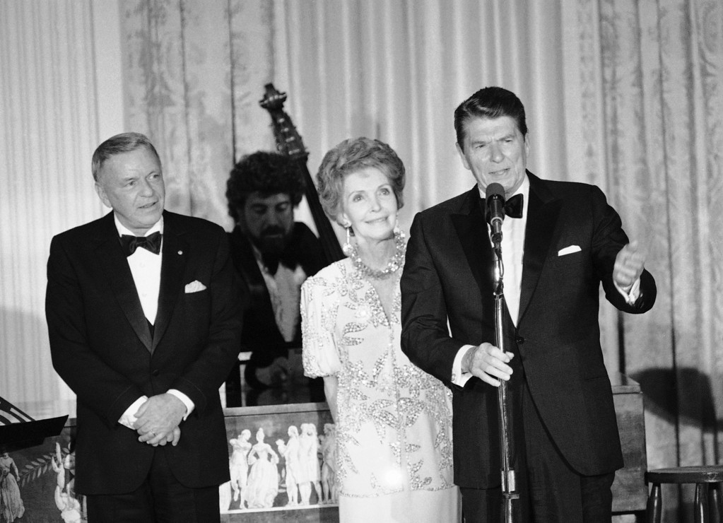 . FILE - In this June 19, 1984, file photo President Ronald Reagan and his Nancy Reagan address a White House State Dinner audience following the performance of singer Frank Sinatra, left.  (AP Photo/Scott Stewart, FILE)