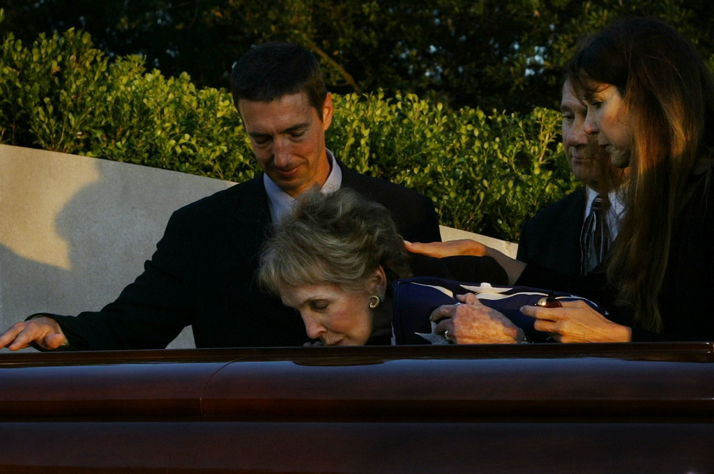 . Nancy Reagan, center, is joined by son Ron Reagan, left, son Michael Reagan, second from right, and daughter Patti Davis as she kisses the coffin bearing her husband former President Ronald Reagan during interment ceremonies for the former president at the Ronald Reagan Presidential Library in Simi Valley, Calif.,  Friday, June 11, 2004. (AP Photo/Bryan Chan, Pool)