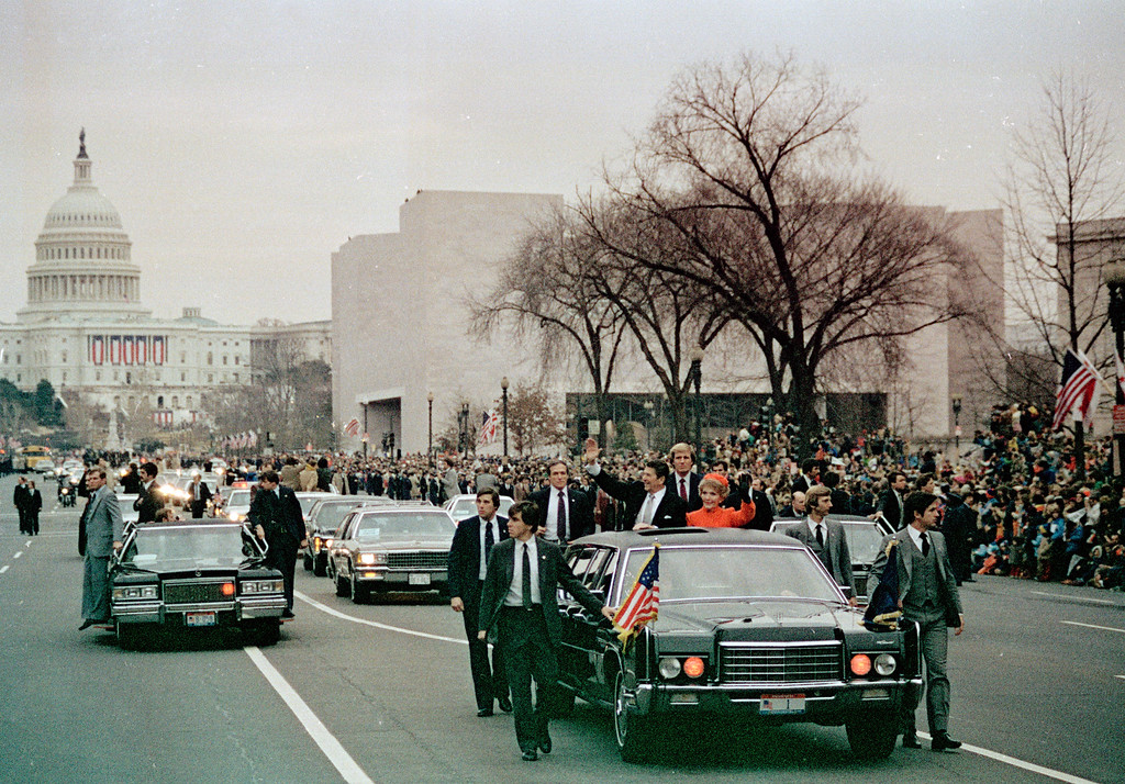 . U.S. President Ronald Reagan, left, and first lady Nancy Reagan wave to the crowd from their limousine as they lead the motorcade down Washington\'s Pennsylvania Avenue on inauguration day, Jan. 20, 1981, following swearing-in ceremony.  The Capitol building is visible in background, left.  (AP Photo)
