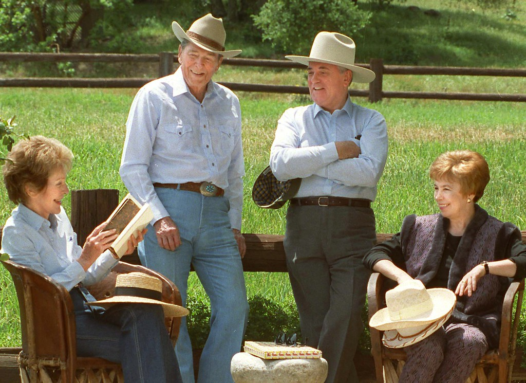 . 5/3/92--Santa Barbara--Former United States President Ronald Reagan, left and former Soviet President Mikhail Gorbachev don cowboy hats while enjoying a quite moment wives Nancy, left and Raisa Sunday on Reagan\'s Rancho del Ceilo, a 688-acre spread in the mountains 30 miles north of Santa Barbara, California. Gorbachev and his wife, Raisa, are on a two-week tour of the United States. (Gus Ruelas/LA Daily News)
