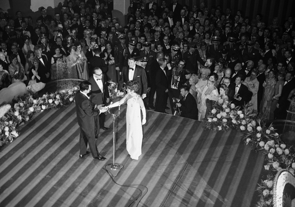 . California\'s 33rd governor, Ronald Reagan, steps to the microphone with wife Nancy,  for a few words on Jan. 6, 1967 in Sacramento\'s inaugural ball.  On the platform with the  governor are:  Jack Benny, Lt. Gov. and Mrs. Robert Finch and Mrs. Nancy Reagan. (AP Photo/Sal Veder)