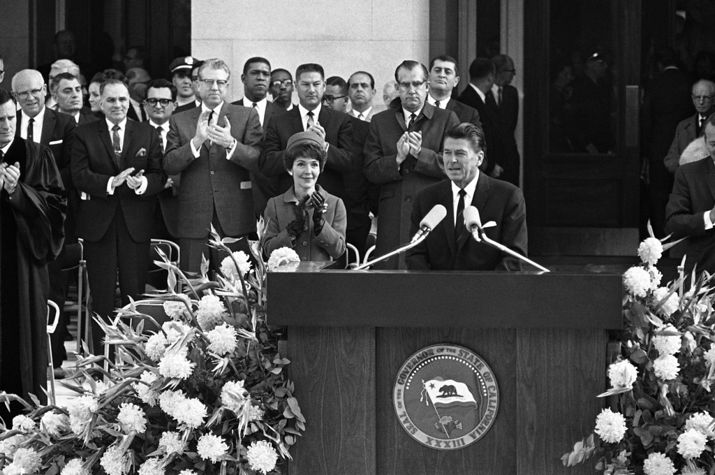 . Ronald Reagan, California�s 33rd Governor, stands at the podium and acknowledges applause following his introduction at inaugural ceremonies on Jan. 5, 1967 on the Sacramento capitol steps in Sacramento, California. To his right is his wife, Nancy. Legislators behind him include, front row: Assemblymen Charles Conrad, R-Sherman Oask; Don Mulford, R-Piedmont; Assembly Minority Leader Robert Monagan, R-Tracy, and Carlos Bee, D-Hayward, speaker pro tem of the Assembly. (AP Photo)
