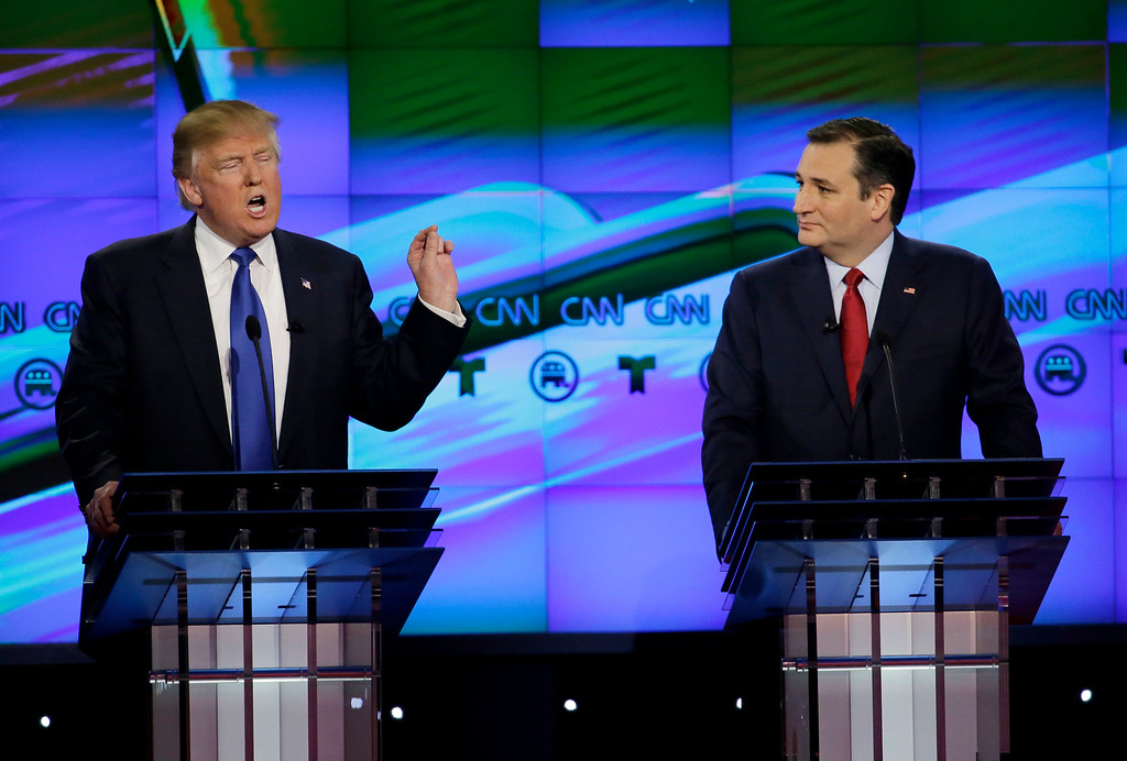 """. FILE - In this Feb. 25, 2016 file photo, Sen. Ted Cruz, R-Texas listen as Donald Trump speaks during a Republican presidential primary debate at The University of Houston in Houston. Cruz announced Friday, Sept. 23, 2016, he will vote for Donald Trump, a dramatic about-face for the Texas senator who previously called the New York businessman a \""""pathological liar\"""" and \""""utterly amoral.\"""" (AP Photo/David J. Phillip, File)"""