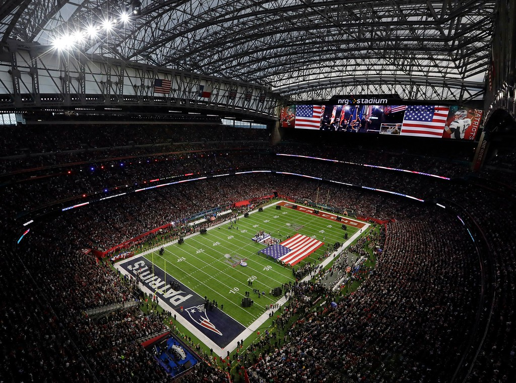 . The American Flag is displayed on the field as Luke Bryan sings the national anthem before the NFL Super Bowl 51 football game between the Atlanta Falcons and the New England Patriots Sunday, Feb. 5, 2017, in Houston. (AP Photo/Morry Gash)