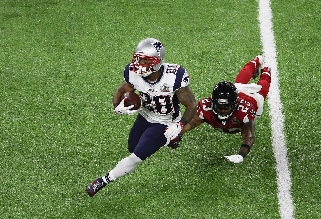 . HOUSTON, TX - FEBRUARY 05: James White #28 of the New England Patriots evades a tackle from Robert Alford #23 of the Atlanta Falcons  during Super Bowl 51 at NRG Stadium on February 5, 2017 in Houston, Texas.  (Photo by Ezra Shaw/Getty Images)