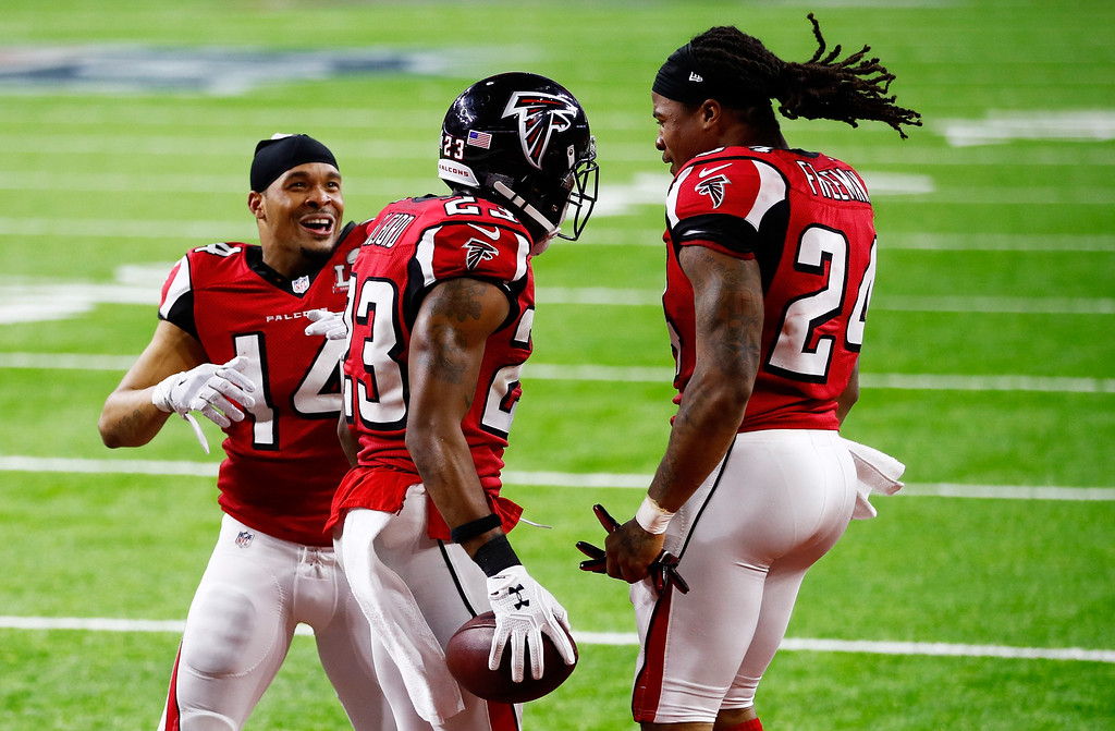. HOUSTON, TX - FEBRUARY 05:  Eric Weems #14, and Devonta Freeman #24 celebrate with Robert Alford #23 of the Atlanta Falcons after Alford scored a touchdown on a 82 yard interception against the New England Patriots during Super Bowl 51 at NRG Stadium on February 5, 2017 in Houston, Texas.  (Photo by Gregory Shamus/Getty Images)