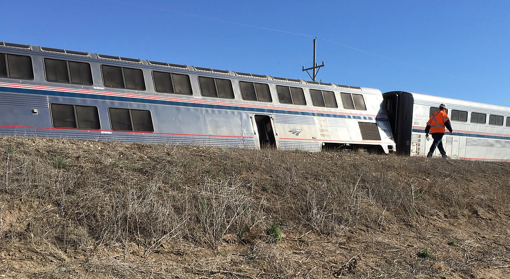 . A railroad worker walks past one of the Amtrak cars that derailed west of Dodge City, Kansas early Monday, March 14, 2016, injuring multiple people who were transferred to hospitals in Garden City and Dodge City, according to a release from Amtrak. The Amtrak train carrying 131 passengers derailed in rural Kansas moments after an engineer noticed a significant bend in a rail and applied the emergency brakes, an official said.   (Oliver Morrison /The Wichita Eagle via AP)