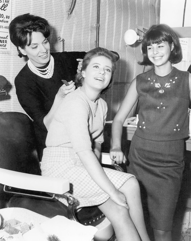". Actress Patty Duke, star of ABC-TV\'s ""The Patty Duke Show,\"" and Colette Daiute, right, who recently won the Miss Teenage America contest, meet at a Hollywood beauty salon as they prepare for their roles on Patty\'s show, Dec. 3, 1965.  Fixing Patty\'s hair is hair stylist Jeanne Bodel. (AP Photo)"